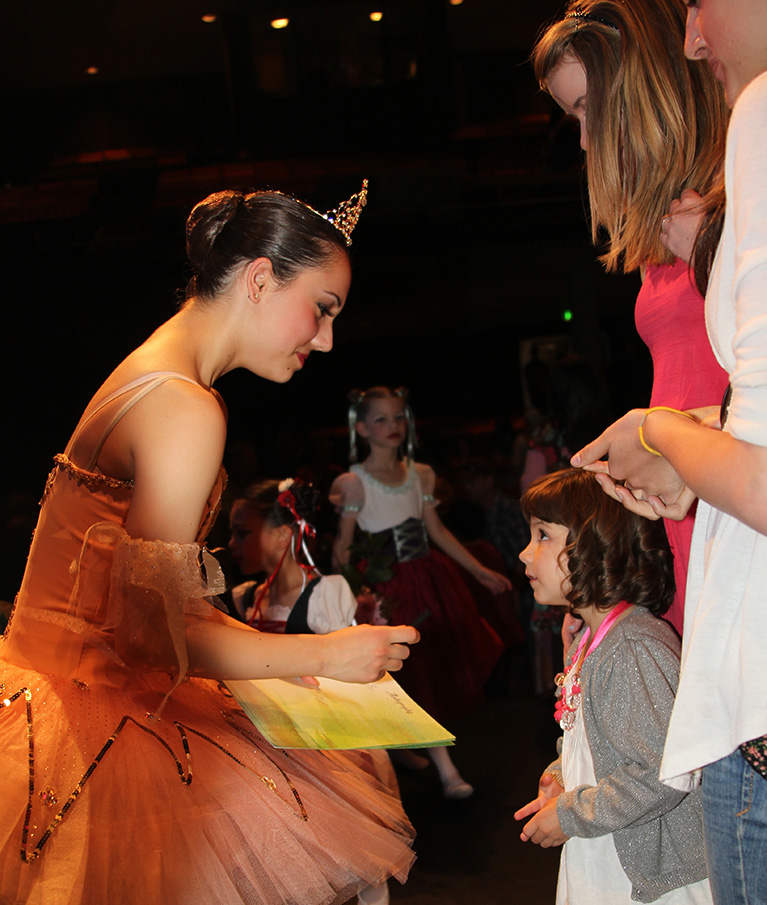 an image of a female performer signing an autograph for a young girl who looks up at her in awe and amazment
