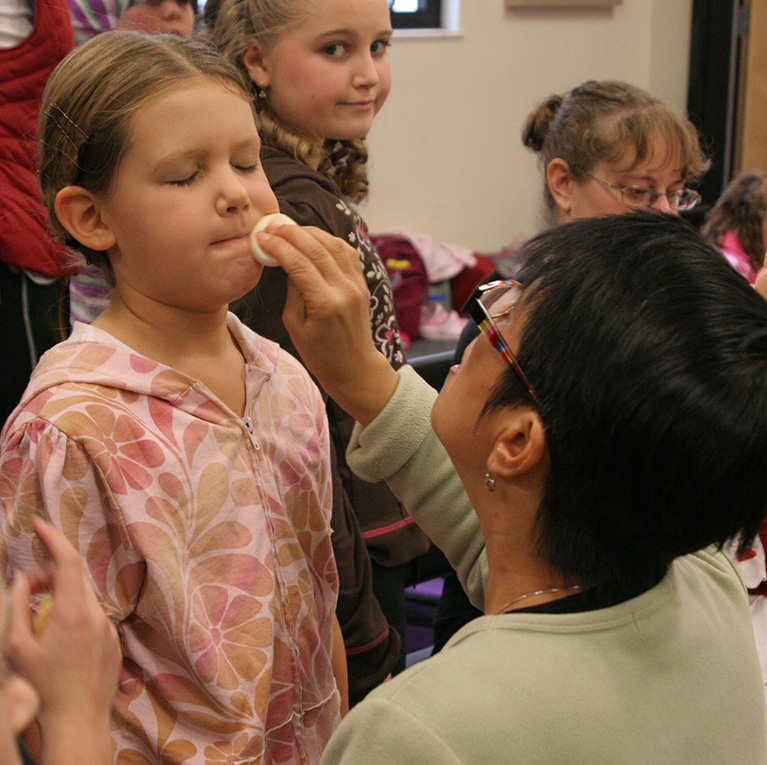 an image of a volunteer applying makeup to a small child performer
