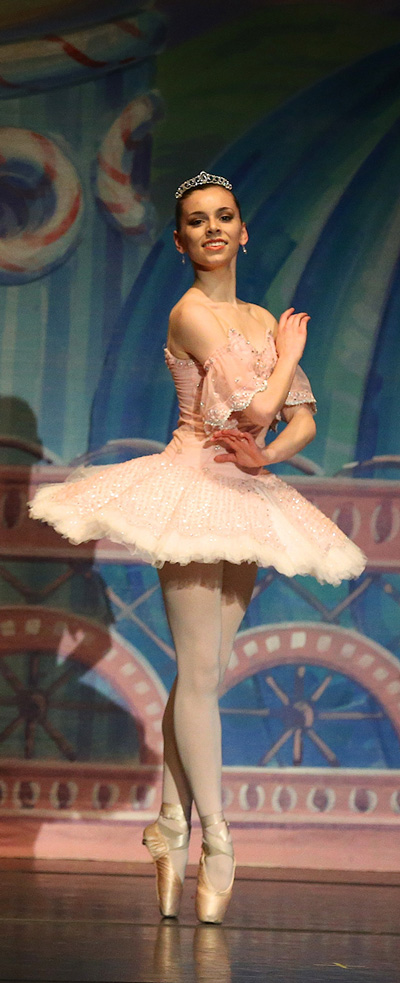 an image of a woman performer twirling in a white dress and smiling